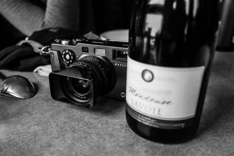 photo noir et blanc d'un appareil photo et d'une bouteille de vin lors de l'ascension du mont blanc par la voir normale