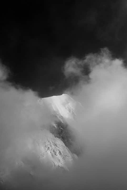 photo noir et blanc du sommet du mont blanc dans les nuages lors de l'ascension par la voie normale